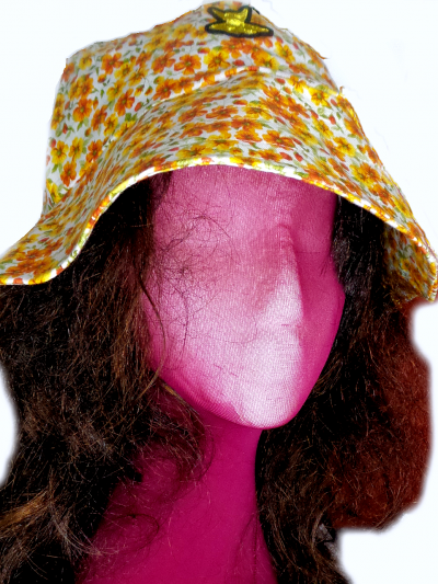 Bucket hat on dummie head and brown hair. Hat printed in yellow flowers in bloom and buds with embroidered gold bee.