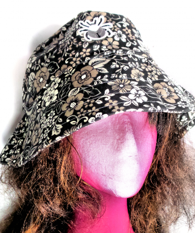 Pink face dummy with brown hair wearing floral print bucket hat in gray hues.