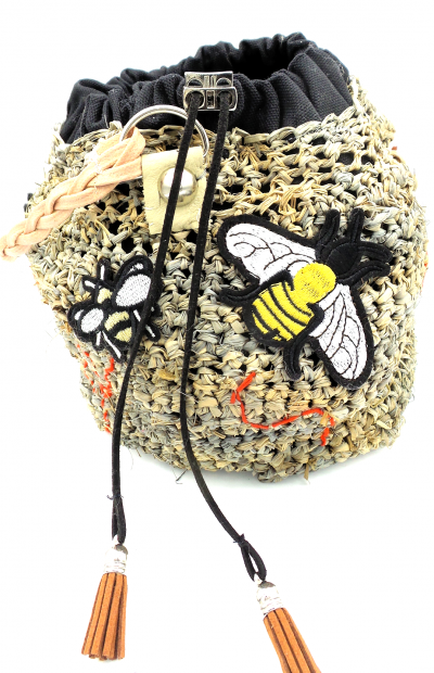 Gray straw bag with various insect patches ironed onto it. Draw string closure ending in tassels. Braided wax linen strap.