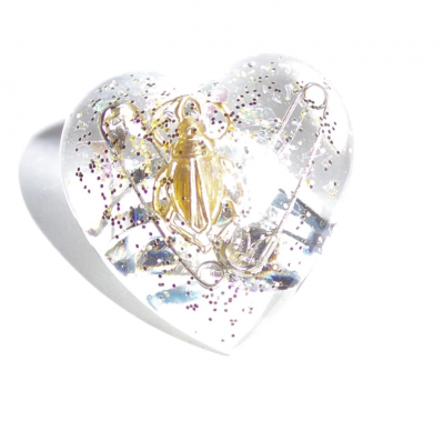 Heart shaped resin ring with bras bug and safety pin trapped inside.