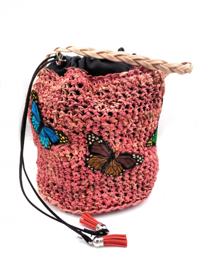 Pink straw bucket bag with draw string closure. Butterfly patches decorate bag. Braided wax linen handle.