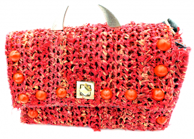 Red straw crossbody bag with silver horn studs, red cone studs and a turnkey latch.
