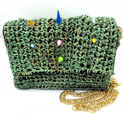 Multiple colored tree spikes decorate a sage green straw crossbody bag with gold chain strap.