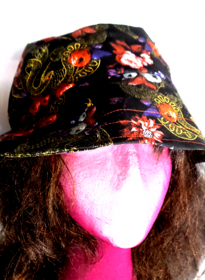 Styrofoam head with curly brown hair wearing bucket hat with snakes, skulls and roses print.